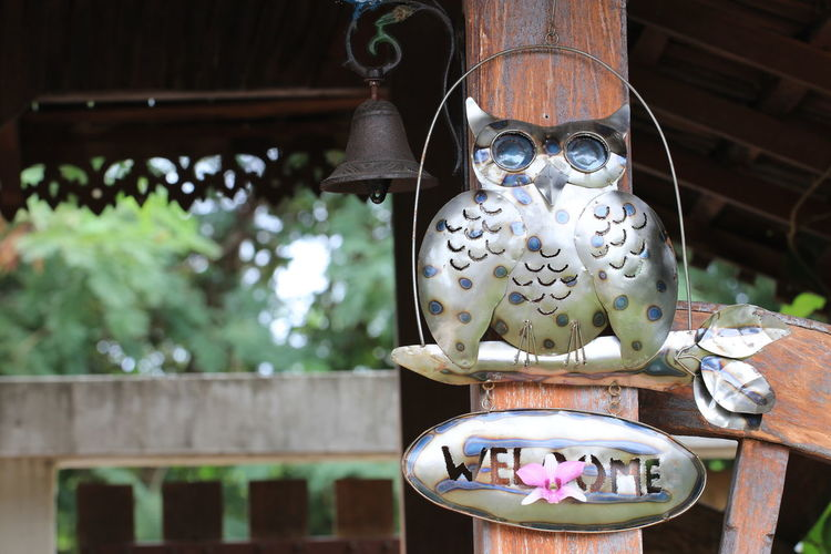 Close up iron owl hanging on wood pillar Hanging Architecture Art And Craft Belief Built Structure Close Up Close-up Craft Creativity Day Decoration Floral Pattern Focus Focus On Foreground Hanging Human Representation Iron Owl Low Angle View No People Outdoors Religion Representation Spirituality Wood - Material Wood Pillar