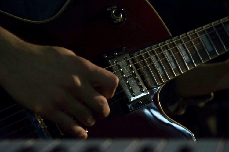 Close-up of hand plucking guitar