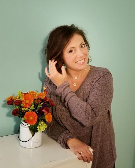 Portrait of smiling woman by flowers in vase on table against wall