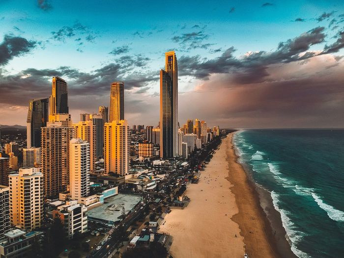 Modern buildings at beach against cloudy sky during sunset