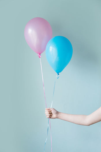 Cropped hand of person holding balloons against turquoise background