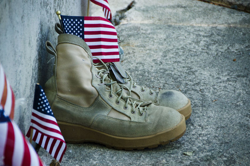 Close-up of shoes with american flags on footpath