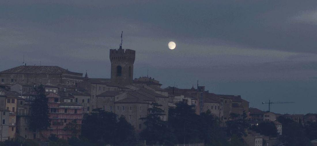 Buildings in town against sky at night