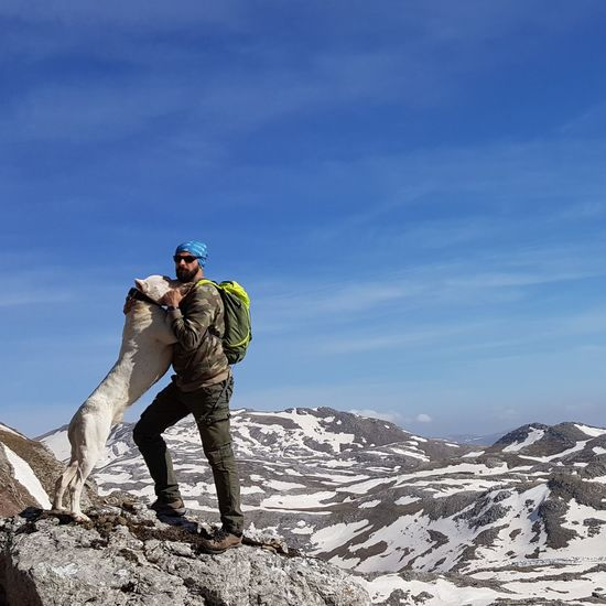 Man standing with dog on snowcapped mountain against sky