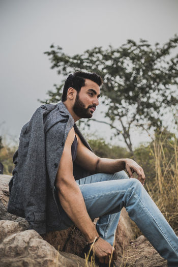 Side view of thoughtful young man sitting on rock against tree