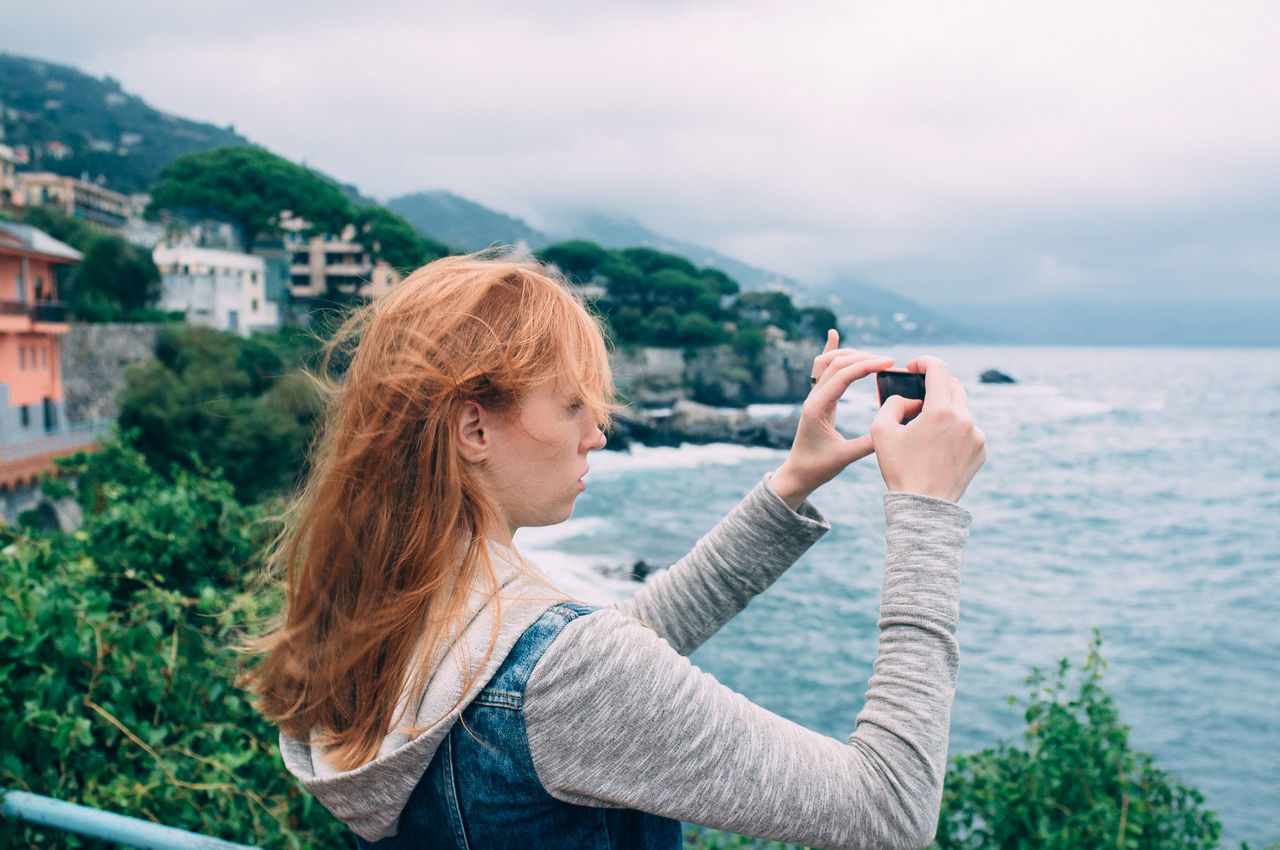 Young woman photographing on promenade