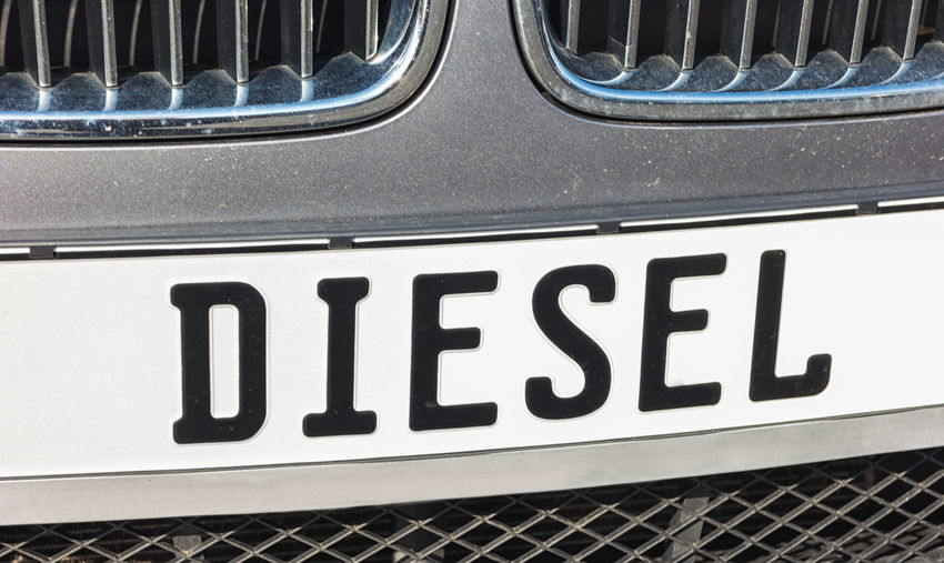 """license plate with """"diesel"""" text - Concept image for the """"Diesel-Gate"""" Cars Diesel-Gate Fossil Fuel Fuel Pump Gas Gasoline Industry License Plate Scandal Transportation Car Close-up Close—up Communication Diesel Fuel And Power Generation Gas Station Grill No People Outdoors Plate Text Transportation"""