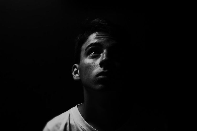 Portrait of teenage boy against black background