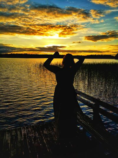 Silhouette woman by lake against sky during sunset