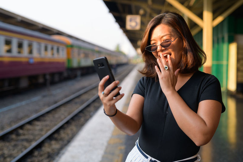 Young woman using mobile phone at bus