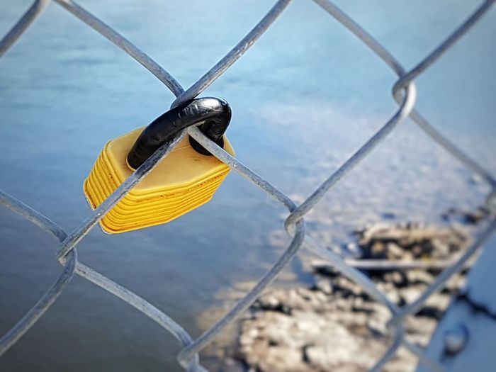 Close-up of padlock hanging from chainlink fence over river