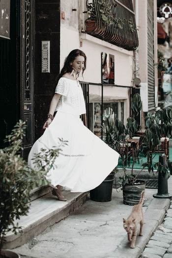 Young hippie woman in white boho clothes walking in the street of istanbul city in summer