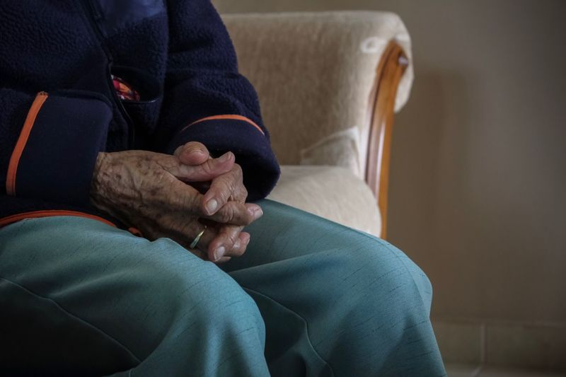 Midsection of person sitting with hands clasped on sofa at home