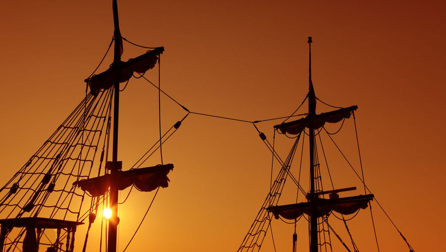 Silhouettes of old-fashioned masts against a twilight sky, suggesting the idea of navigation. Sunset Sky Silhouette Orange Color Sailboat Rope Nautical Vessel Low Angle View No People Transportation Mast Outdoors Sun Mode Of Transportation Navigation Abstract Concept