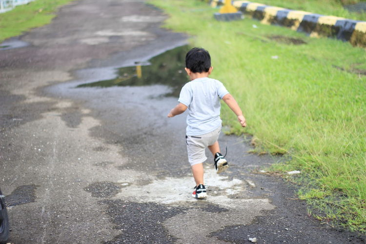 Rear view of boy running on road