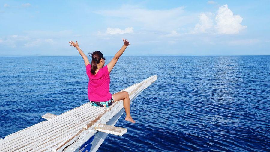 Full length of girl relaxing on sea shore against sky