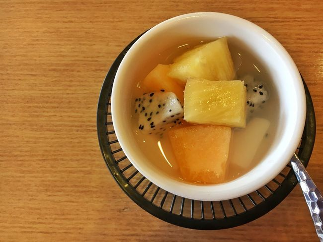 mixed fruits in syrup on table Backgrounds Bowl Cantaloupe Close-up Dessert Dragon Fruits Food Food And Drink Freshness Healthy Eating High Angle View Mixed Fruits Pineapple Syrup Table Wood
