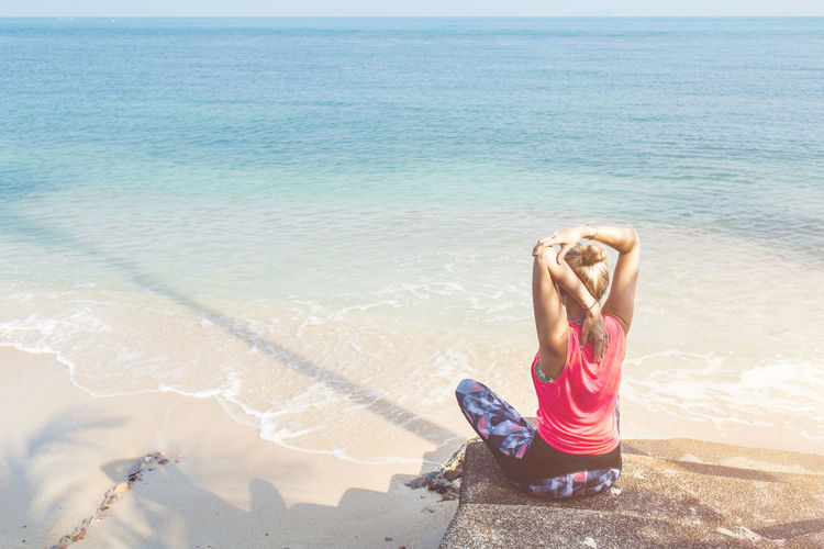 Fitness Woman stretching at the beach Beach Beauty In Nature Day Exercising Flexibility Horizon Over Water Leisure Activity Lifestyles Nature One Person Outdoors Real People Sand Scenics Sea Shore Sky Vacations Water Young Adult Young Women