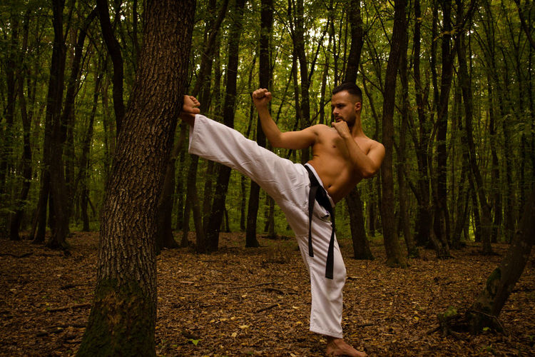 Shirtless man practicing karate against trees in forest