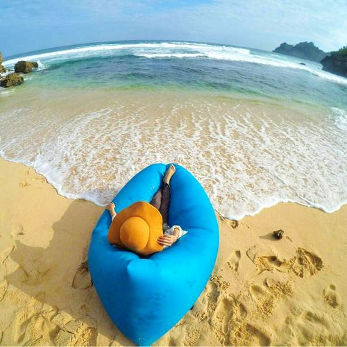 Woman Relaxing In Bean Bag At Beach