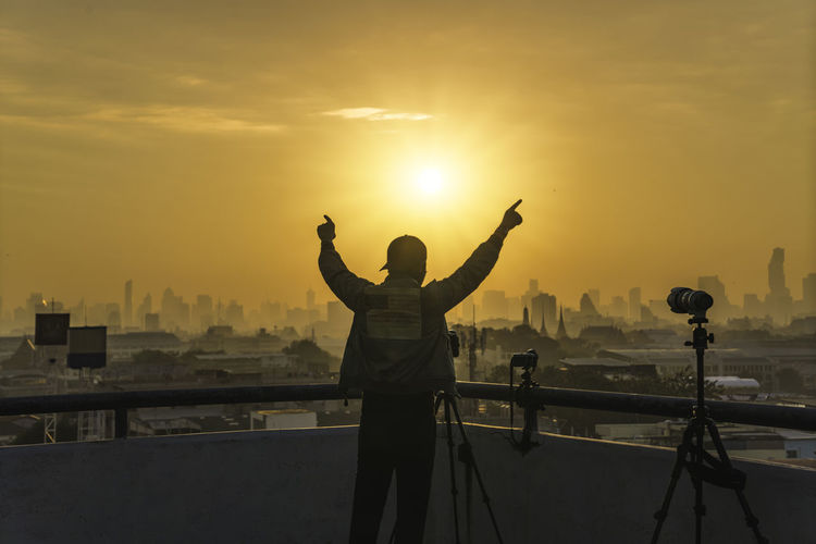 Full length of man standing by cityscape against sky during sunset