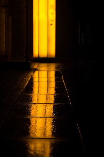 Low angle view of hallway with yellow light