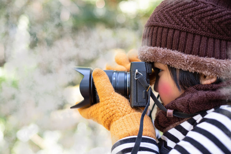 Portrait of a cute little girl in wool hat taking a picture with digital camera