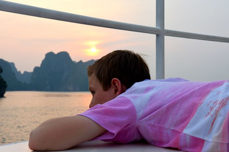 Vietnam Halong Bay Looking At Sunset Relaxing On Moving Boat Headshot Lifestyles Loneliness Person Relaxation Sun Sunlight Sunset Weekend Activities Young Adult