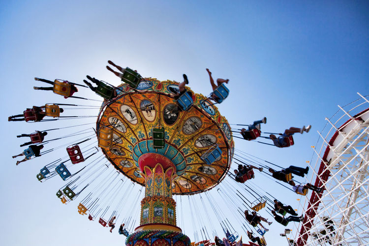 Low angle view of people on chain swing ride against clear sky during sunny day