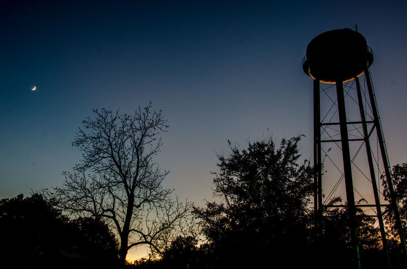 50/50 Moon Trees Backlit Beauty In Nature Blue Long Exposure Low Angle View Moon Nature Night No People Outdoors Silhouette Sky Small Town Sun Sun And Moon Sunset Tree Water Tank Water Tower - Storage Tank Watertower