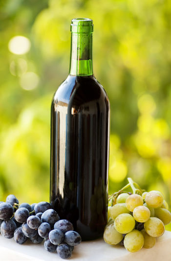 Close-up of wine bottle amidst grapes on table