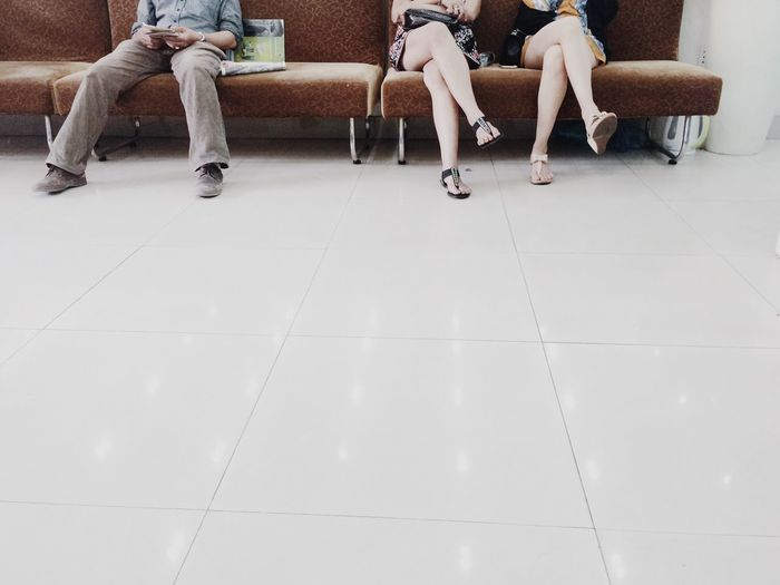 Low section of people sitting on sofa