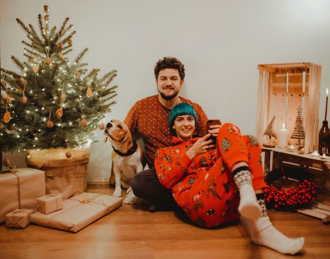 Portrait of smiling couple with dog sitting by christmas tree at home