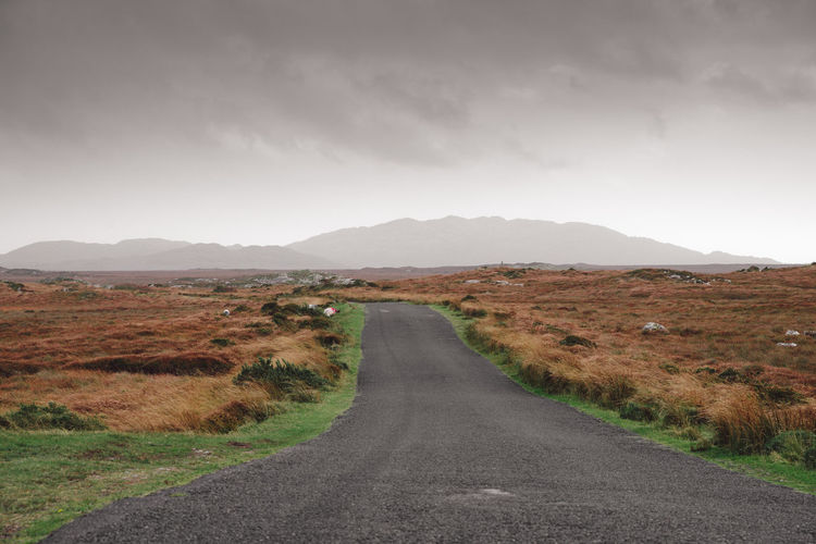 empty road leading into the Connemara Nationalpark in Ireland Connemara Connemara National Park Connemara, Landscape, Lake, Ireland, Galway Ireland Ireland Landscapes Irish Landscape Solitude Wilderness Bog Tree Empty Road Road Direction Transportation Mountain Landscape The Way Forward Sky Environment Tranquility Nature Scenics - Nature Tranquil Scene Beauty In Nature No People Non-urban Scene vanishing point Mountain Range Land Diminishing Perspective Cloud - Sky Outdoors