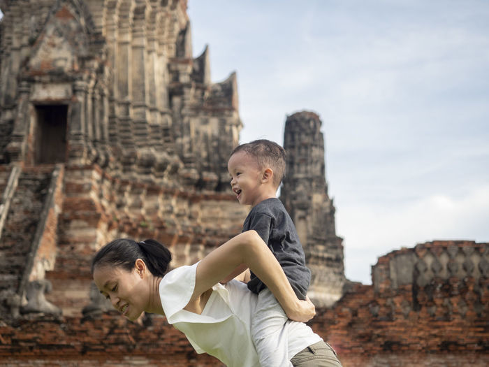 Side view of mother carrying son on back against ancient temple
