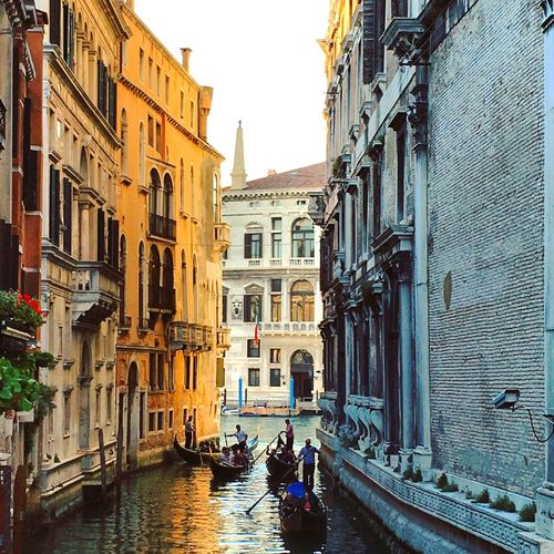 Men in gondolas on grand canal amidst buildings in town