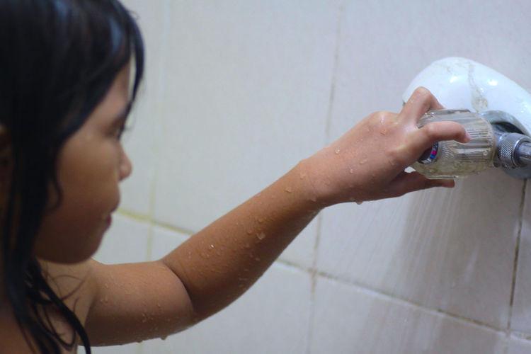 Girl turning shower knob while taking bath in bathroom