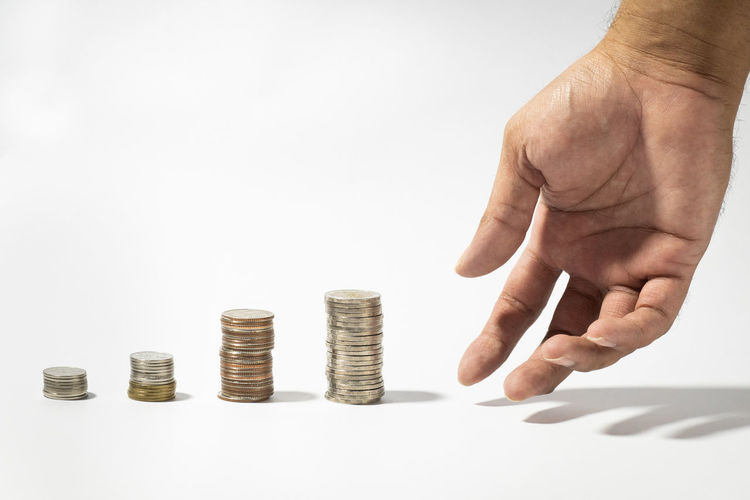 Cropped image of hand holding coin stack against white background
