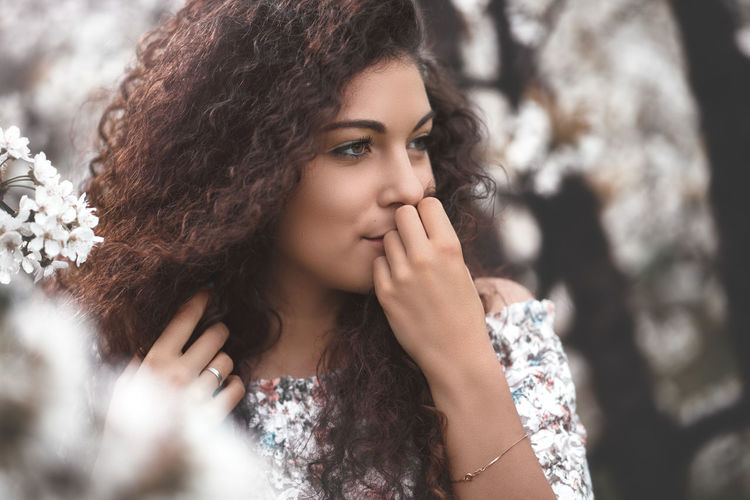 Portrait of beautiful young woman looking away outdoors