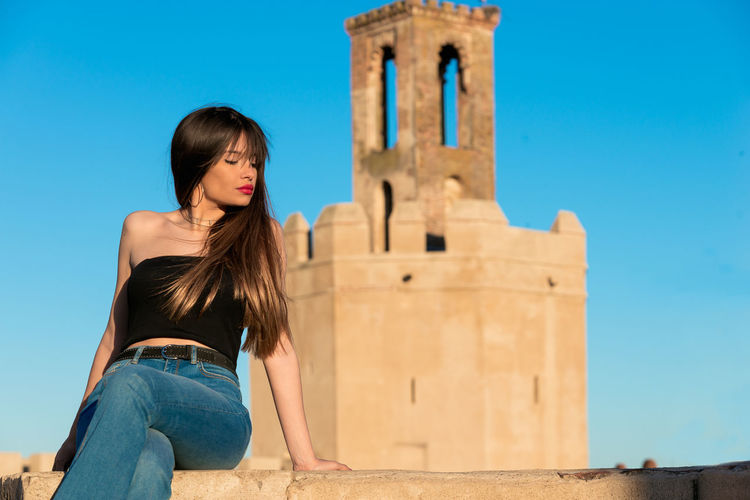 Young woman sitting against historical building