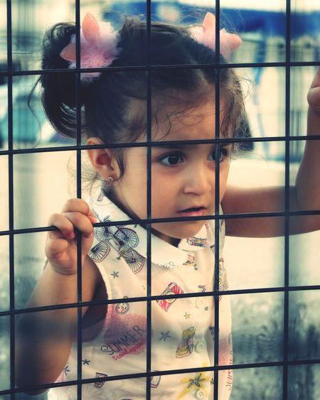 Girl Seen Through Fence