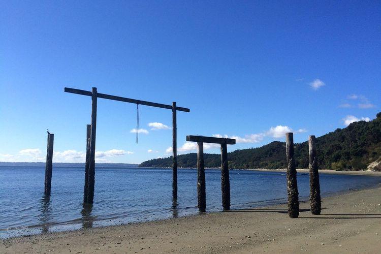 Wooden poles on beach against blue sky