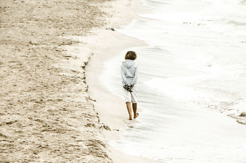 Rear view of person walking on sand
