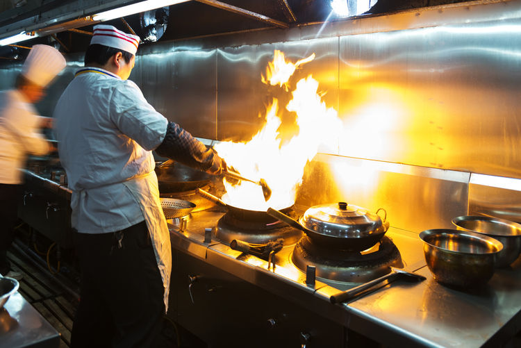 Chef cooking with flame in commercial kitchen at restaurant