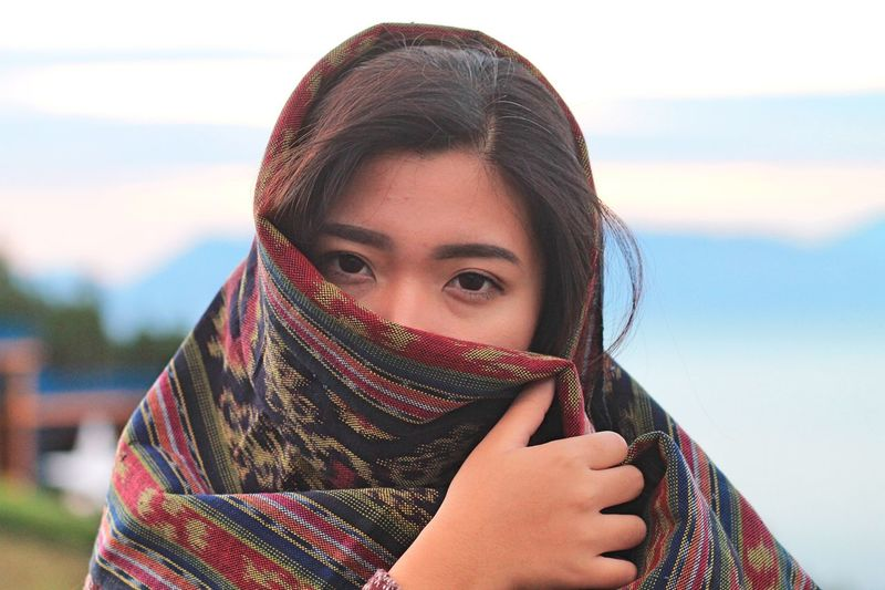 Portrait of woman covering face with shawl