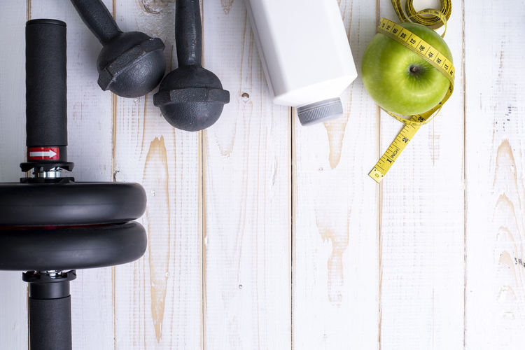 Close-up of granny smith apple and exercise equipment on table