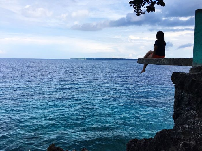 Sitting on the edge where everything you see is blue. To the all blue Sea One Person Water Full Length Sky Leisure Activity Outdoors Horizon Over Water Real People Day Cloud - Sky Nature Vacations Beauty In Nature Mid-air Scenics Jumping Lifestyles Adventure Sitting