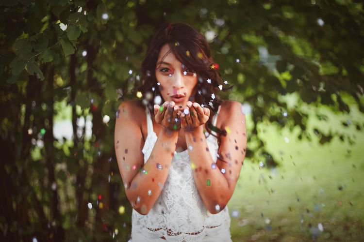 Portrait Of Young Woman Blowing Confetti While Standing Against Trees In Park