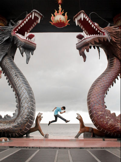 Man Jumping At Beach Seen Through Dragon Statues Against Sky