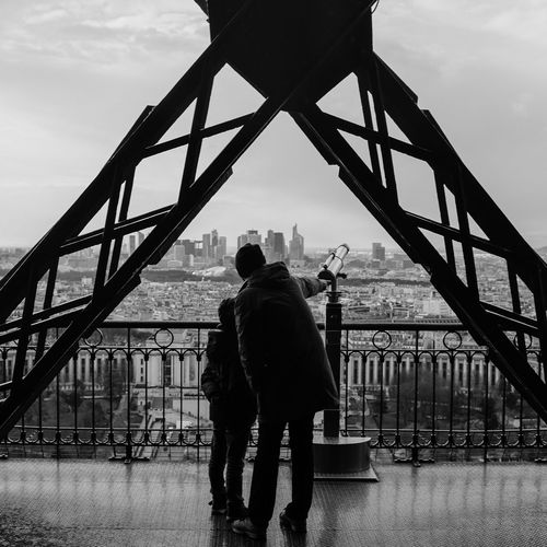 Rear view of man with son by coin-operated binoculars at eiffel tower